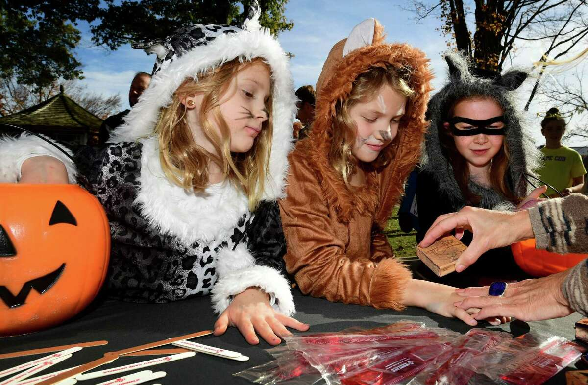 Emma Duffy and Margot Radecki, both 7 of Norwalk, and Emma Nicoletta, 7 of Wilton, get their hands stamped as hundreds of children fan out to trick-or-treat in Wilton Center Saturday, October 26, 2019, in Wilton, Conn. Wilton is one of many towns considering revamping Halloween plans in light of the 2020 pandemic.