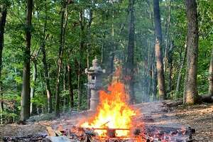 A fire burns in the woods behind a Weston home on Wednesday morning.