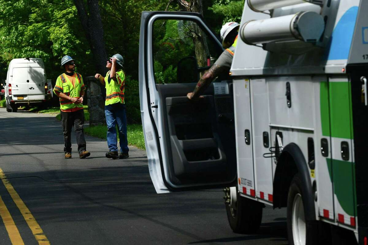 Eversource workers inspect lines along Comstock Hill Road Wednesday, August 12, 2020, in Norwalk, Conn.