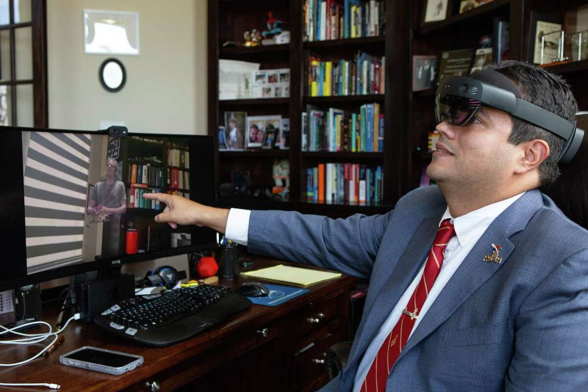Wearing his mixed reality headset, Fernando De La Peña Llaca points to the screen which shows what he sees through the smart glasses - a holographic representation of Nathan Ream, software architect, who can speak and interact with Peña Llaca in his office.