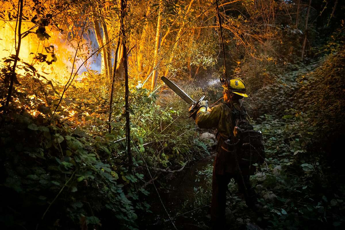 A National Guardsman cuts a fire line on the West Zone Fire, part of the North Complex Fire, on Thursday, Sept. 10, 2020, near Feather Falls, Calif. Wildfires in California, Oregon and Washington State have killed at least seven people, and there are growing fears more have died in towns that have been destroyed. (Max Whittaker/The New York Times)