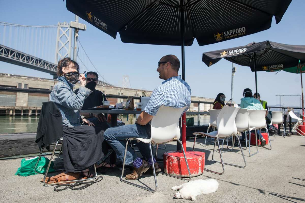 (Left to right) Ellen Lerner, Floyd Stone and Ed Shapiro enjoy their lunch on the outdoor patio of Red's Java House on Pier 30-32 in San Francisco, California on Sept. 16, 2020.