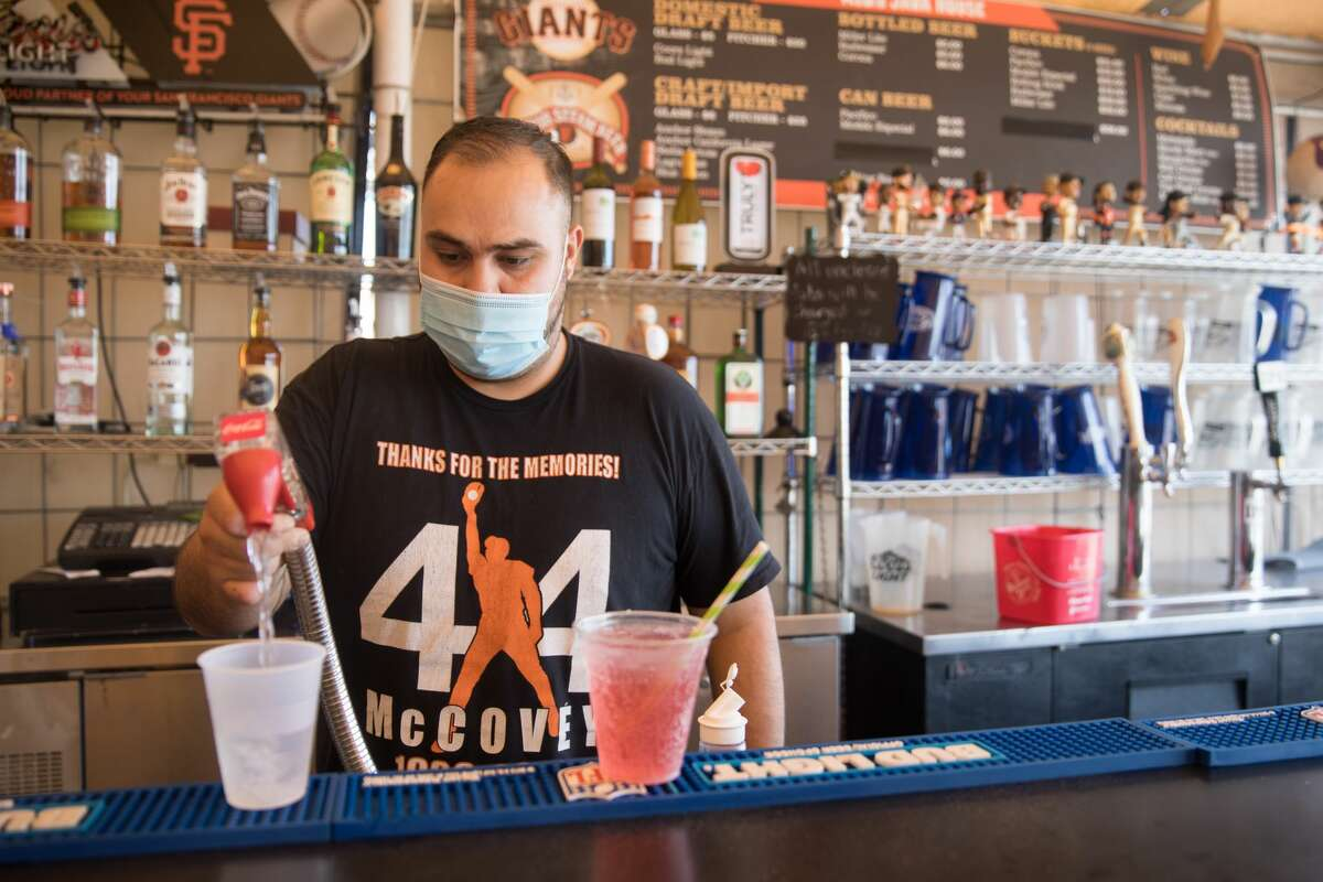 Employee Carlos Medina pours drinks at the bar of Red's Java House on Pier 30-32 in San Francisco, California on Sept. 16, 2020.