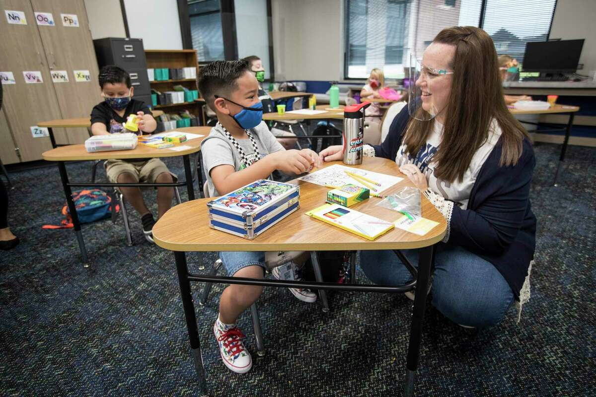 Katy Independent School District is looking for volunteer parents to review new instructional materials for the 2021-2022 school year. Here, first grade teacher Jessica Branch kneels down to talk to Noah Spencer as she works with her students on the first day of in-person classes at McElwain Elementary School on Tuesday, Sept. 8, in Katy.