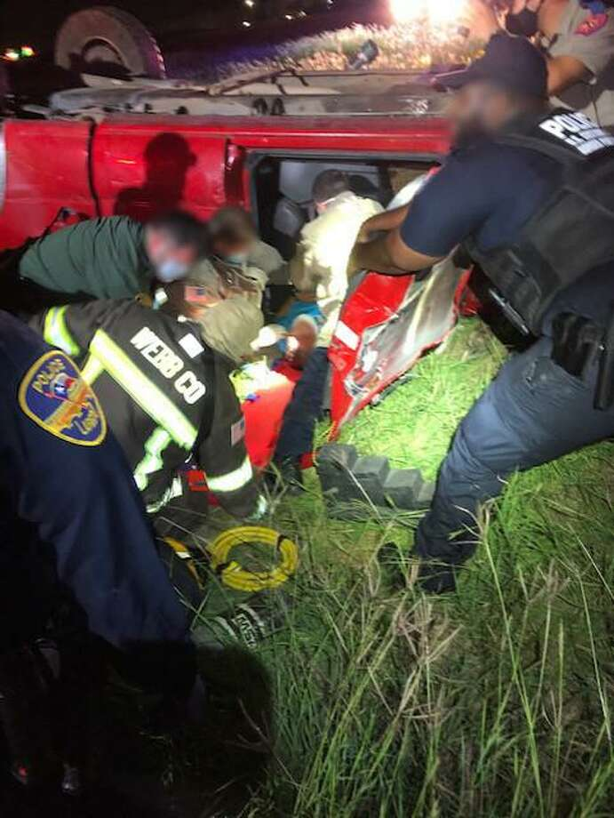 First responders are seen extracting a driver who was involved in a rollover crash in north Laredo early Thursday. The motorist was medically cleared at the scene. Photo: Courtesy Photo /U.S. Border Patrol