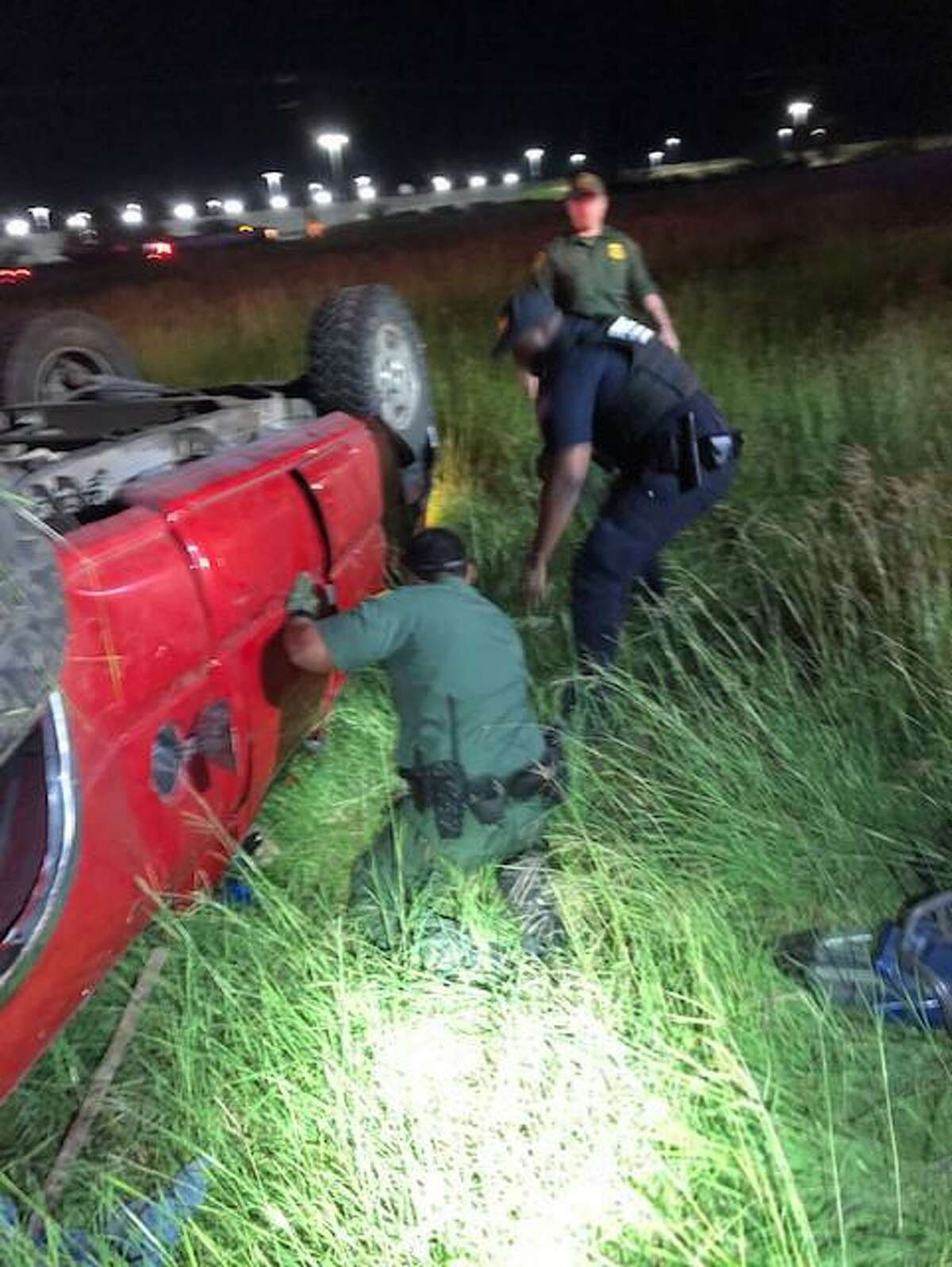 U.S. Border Patrol agents and a U.S. Customs and Border Protection officer are seen assisting a driver who was involved in a rollover crash in north Laredo early Thursday. The motorist was medically cleared at the scene.