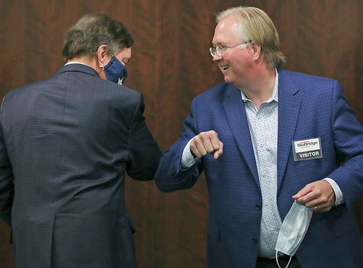 Graham Weston, right, chairman of Community Labs, bumps elbows with Bruce Bugg Jr., vice chairman of Community Labs, a new nonprofit that they said will deliver faster results of coronavirus tests in San Antonio. They spoke at a news conference Thursday, Sept. 17, 2020.