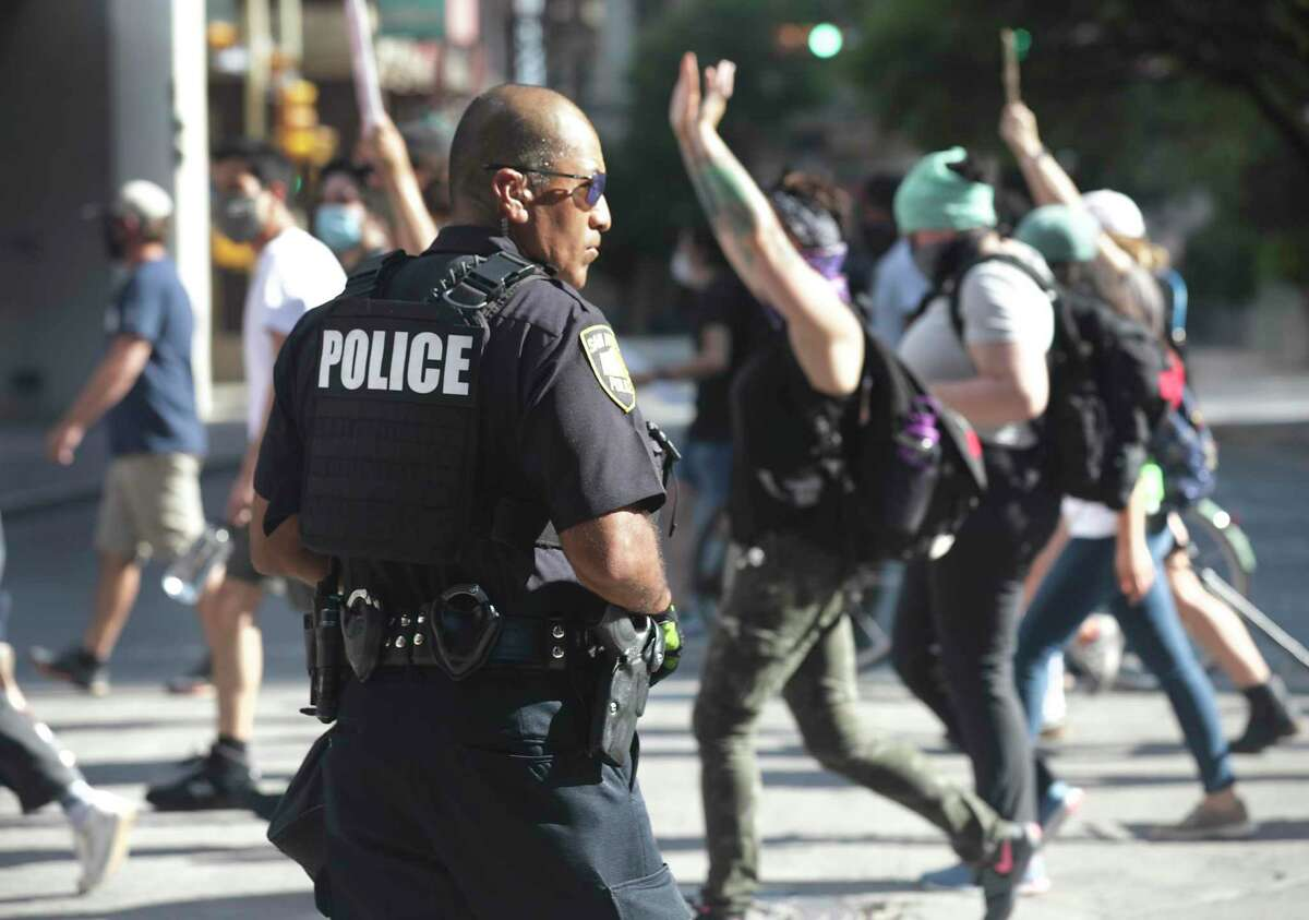 Protesters march downtown past a San Antonio Police officer in this June, 3, 2020, photo.