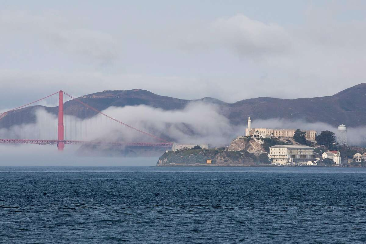 The Golden Gate Bridge and Alcatraz Island sit in a layer of fog under blue skies seen from Treasure Island in San Francisco, Calif. Wednesday, September 16, 2020. Air quality has improved drastically across the Bay Area following almost a week of smoky skies choking the region due to multiple wildfires burning across the West Coast.