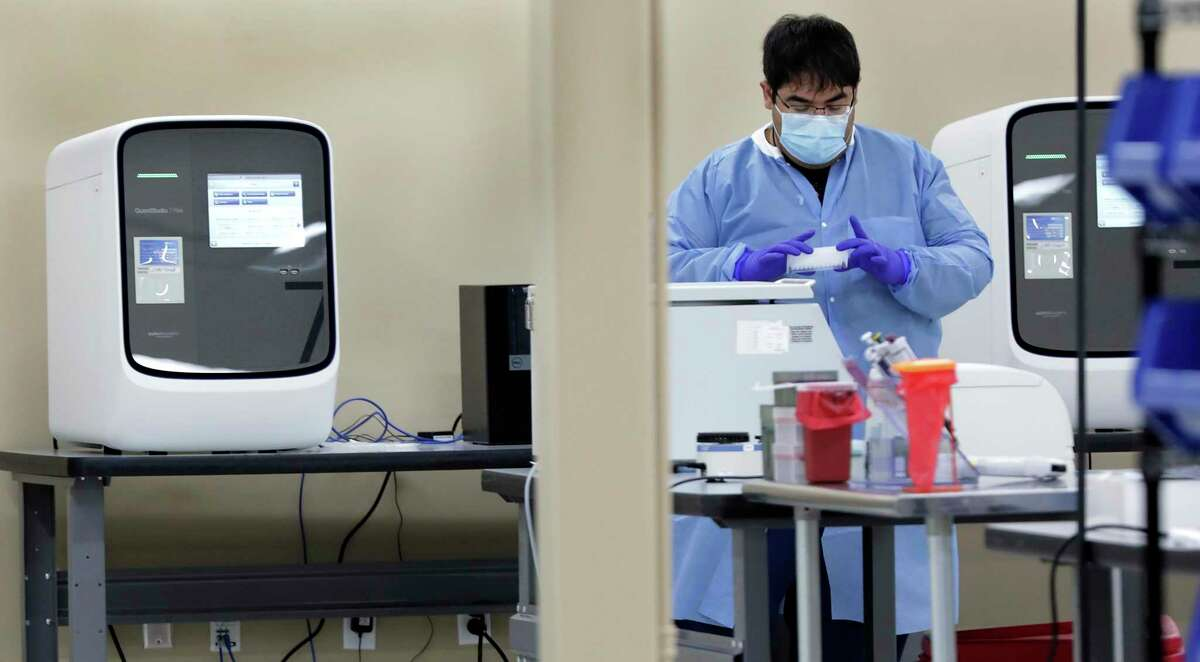Alejandro Trevino prepares testing instruments to be used in the Quant Studio 7 Flex testing machine at left and behind him. The machine can run 379 tests at a time. On Sunday, the Metropolitan Health District reported 116 new cases and one new death.