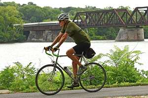 A man rides a bicycle along the Mohawk-Hudson Bike Trail at the Corning Preserve as a train traverses a bridge across the Hudson River on Thursday, Sept. 17, 2020 in Albany, N.Y.  (Lori Van Buren/Times Union)