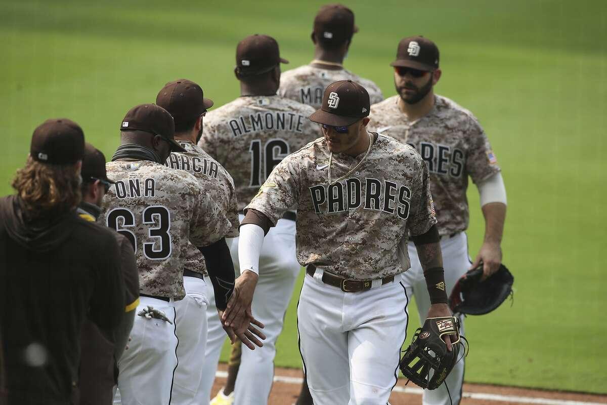 San Diego Padres third baseman Manny Machado high fives teammates after beating the San Francisco Giants in a baseball game Sunday, Sept. 13, 2020, in San Diego. (AP Photo/Derrick Tuskan)