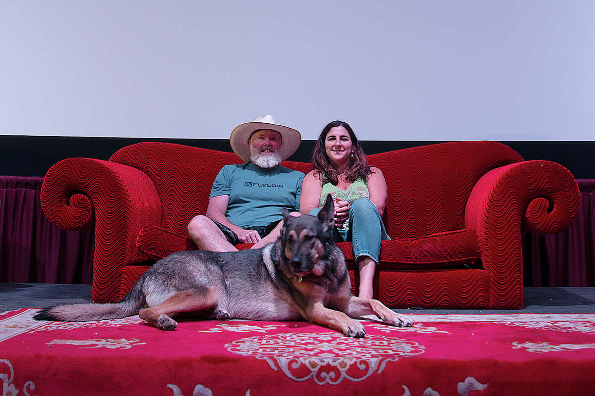 Steven and Melissa Siig, co-owners of the Tahoe Art Haus and Cinema, sit inside the theater with their dog.