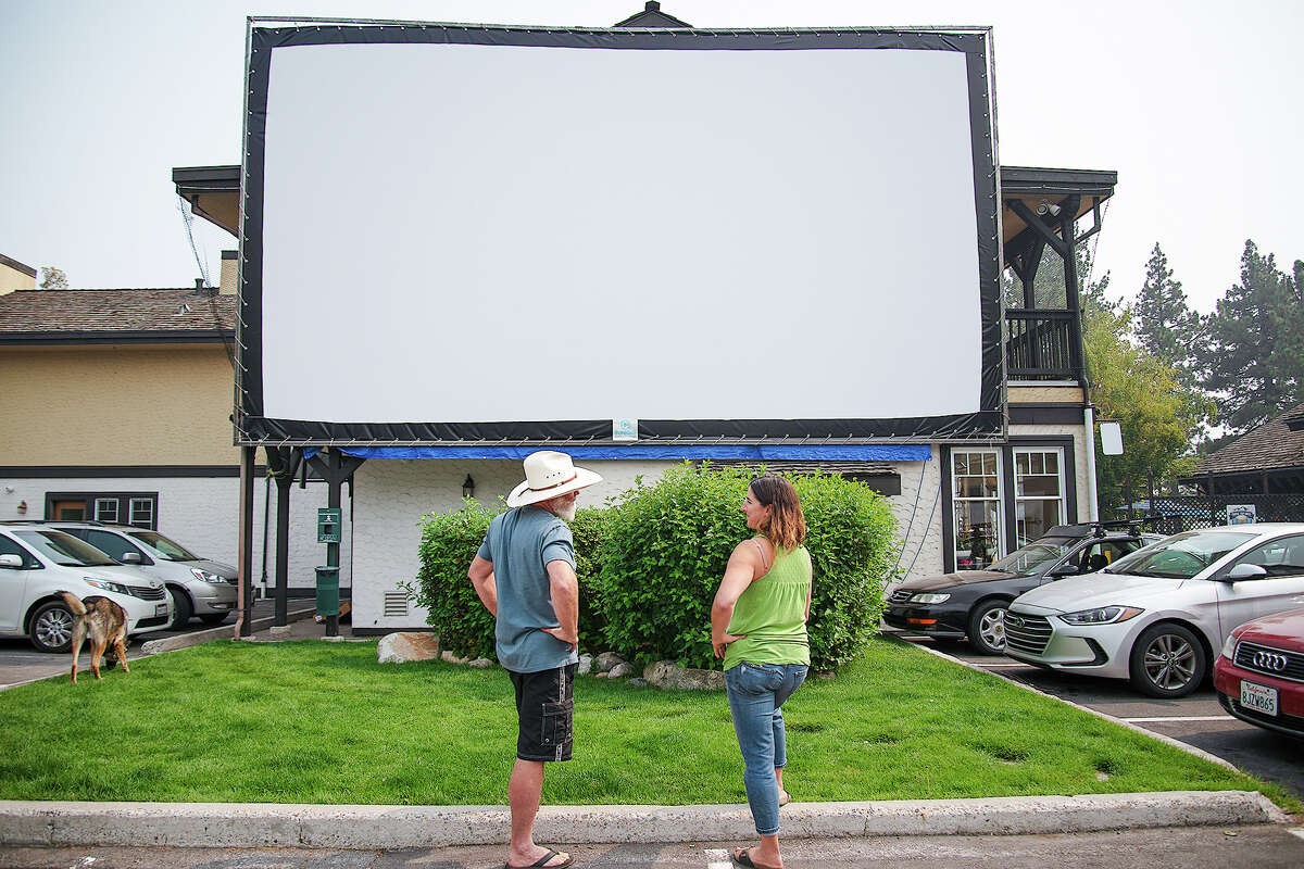 Steven and Melissa Siig in front of their new Drive-In screen in the parking lot of the Cobblestone Center.
