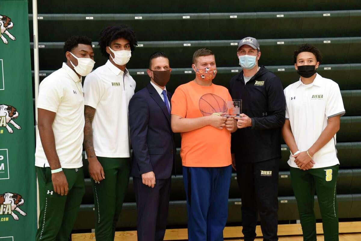 New York State Assemblyman Angelo Santabarbara, third from left, stands with his son Michael as he presents the 2020 Autism Action Award to head coach Carmen Maciariello, second from right, and representatives of the men's basketball team Jalen Pickett, left, Manny Camper, second from left, and Jordan King at Siena College on Thursday, Sept. 17, 2020 in Loudonville, N.Y. Santabarbara was awarding the team for their ongoing support of individuals with Autism Spectrum Disorder. The players from left are Manny Camper, Jalen Pickett and Jordan King. (Lori Van Buren/Times Union)