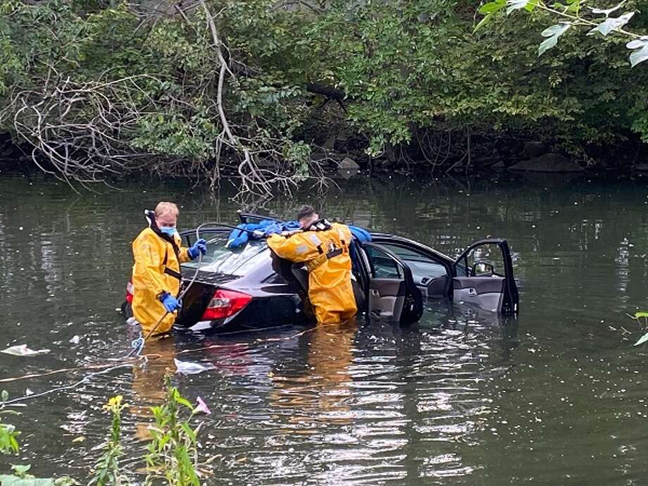 Stamford firefighters help rescue a woman who drove her car into the Rippowam River in downtown Stamford on Monday morning. Photo: Stamford Fire Department