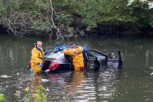 Stamford firefighters help rescue a woman who drove her car into the Rippowam River in downtown Stamford on Monday morning.