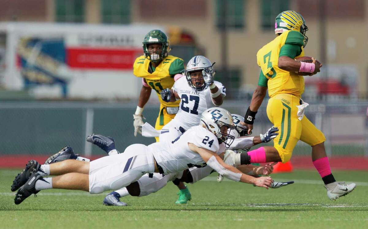College Park defensive back Curt Evangelister (27), linebacker Dylan Hazen (24) and defensive back Perry Irchirl (5) dive after Klein Forest quarterback Delvin Jones (3) as hie picks up a two-gain gain on third down forcing a punt during the first quarter of a District 15-6A high school football game at Klein Memorial Stadium, Friday, Oct. 4, 2019, in Spring.