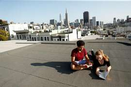 Santosh Vadlamani and Ally Sillins read on the roof of their home in San Francisco, Calif., on Wednesday, September 16, 2020.  The couple have bucked the trend by purchasing a home in San Francisco.