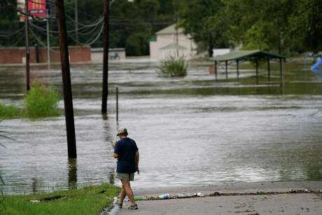 Brenda Davenport holds her dog Harley as floodwaters cover a road, Thursday, Sept. 17, 2020, in Brewton, Ala. Rivers swollen by Hurricane Sally's rains threatened more misery for parts of the Florida Panhandle and south Alabama on Thursday, as the storm's remnants continued to dump heavy rains inland that spread the threat of flooding to Georgia and the Carolinas.(AP Photo/Gerald Herbert)