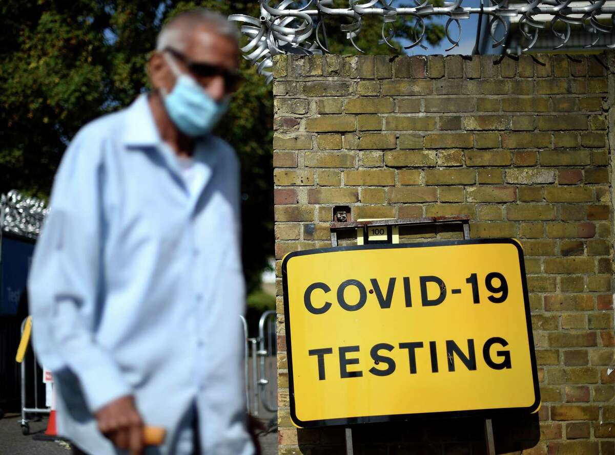 A man wearing a face covering due to the COVID-19 pandemic, waks past a sign outside a novel coronavirus walk-in testing centre in East Ham in east London, on September 17, 2020.