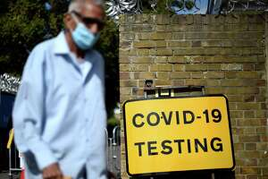"A man wearing a face covering due to the COVID-19 pandemic, waks past a sign outside a novel coronavirus walk-in testing centre in East Ham in east London, on September 17, 2020. - British Prime Minister Boris Johnson said Thursday he could close pubs earlier to ""stop the second hump"" of coronavirus cases, comparing the country's trajectory of resurgent transmission to a camel's profile. But the prime minister has faced stinging criticism this week over the failure to achieve the ""world-beating"" testing and tracing system he promised by the summer. (Photo by DANIEL LEAL-OLIVAS / AFP) (Photo by DANIEL LEAL-OLIVAS/AFP via Getty Images)"
