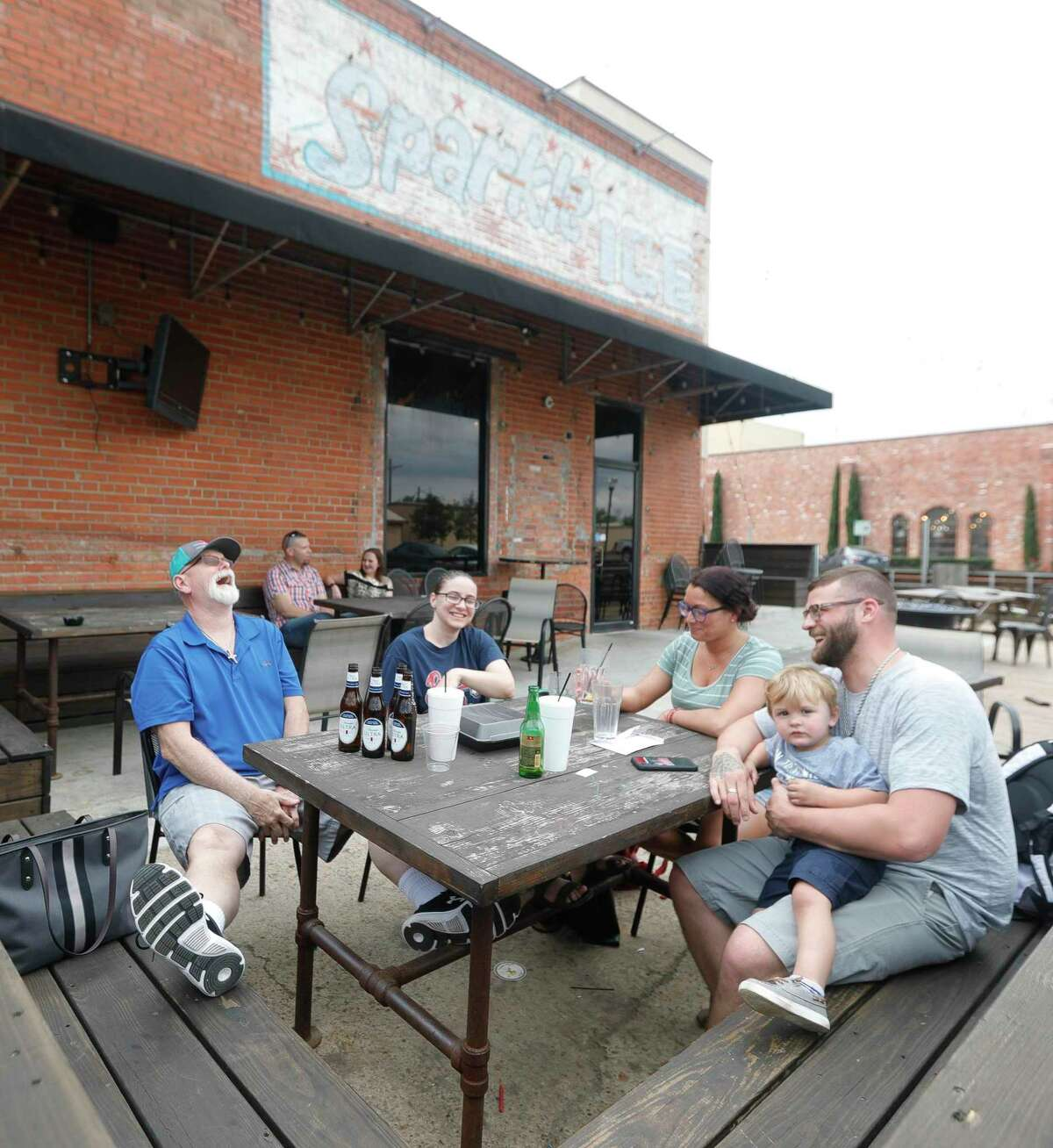 """Rodney Diel, left, shares a laugh with Jessica Wiley, Brittney Bottoms, Dalton Demny and his two-year-old son, Deklyn, as the family enjoys an afternoon at Pacific Yard House, Wednesday, March 18, 2020, in Conroe. Gov. Greg Abbott announced Thursday, Sept. 17, that most of Texas will be able to loosen some coronavirus restrictions, allowing many businesses - including restaurants - to increase their capacity to 75%, as soon as Monday, Sept. 21. At the same time, Abbott said the state was not yet ready to reopen bars, saying they are """"nationally recognized as COVID-spreading locations."""" He stressed, though, that the state is looking for ways to let bars reopen safely."""