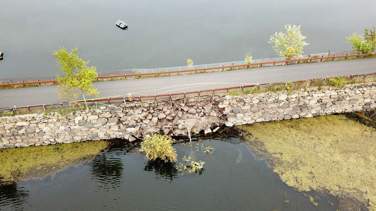 The embankment that runs across Rockwood Lake in backcountry Greenwich has partially collapsed, forcing the road to close.