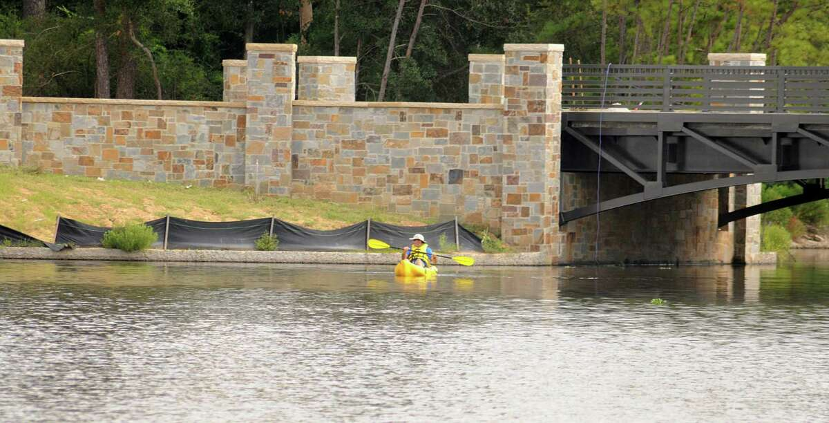 A kayaker on Lake Woodlands passes the new bridge that will connect Mitchell Island, on the east side of Lake Woodlands, located at Timberloch Place and Majestry Row.