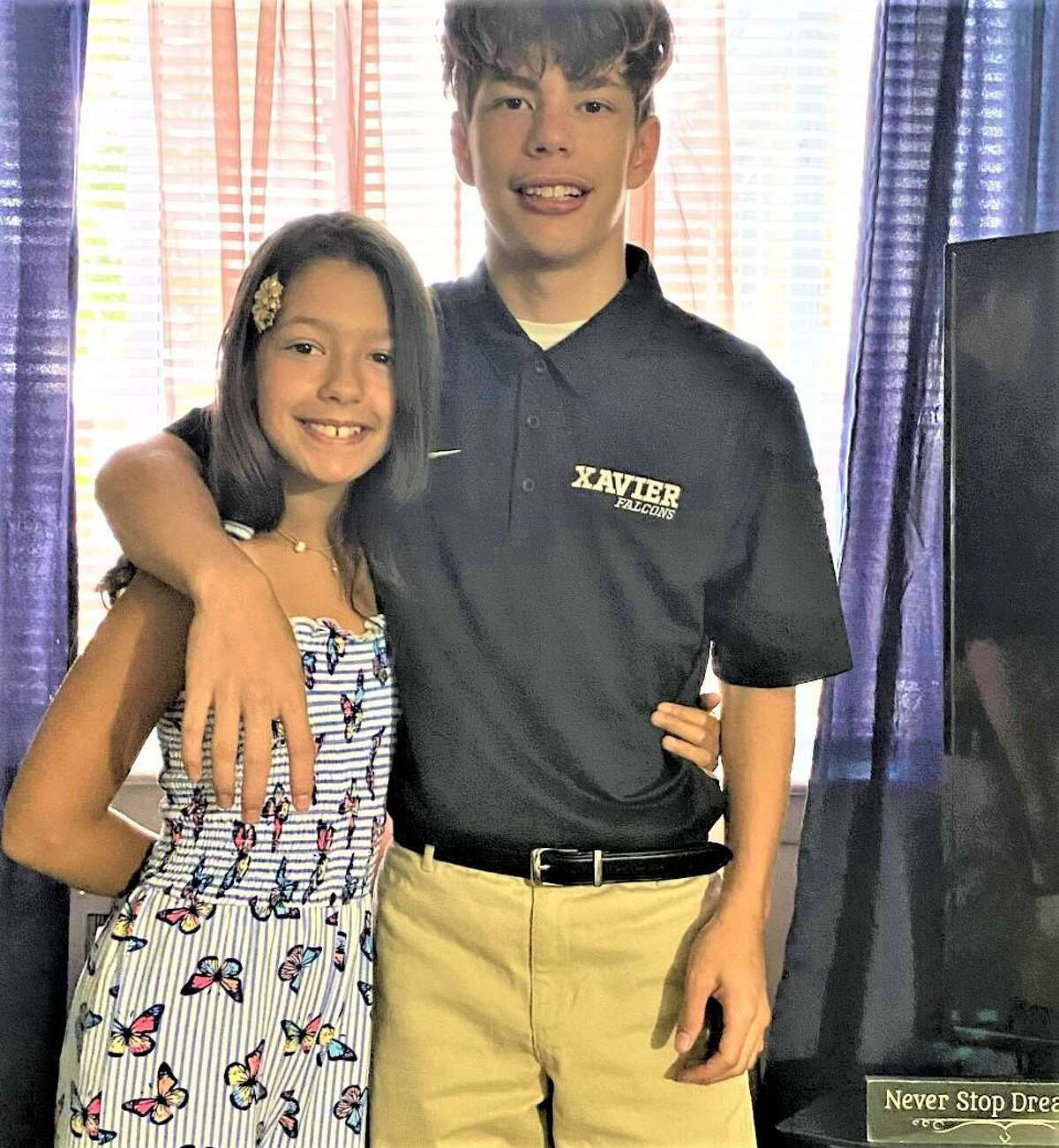 Xavier High School ninth-grader Lucas Rivera, 15, right, of Middletown, poses for a photograph before school Thursday with little sister Annabella Blanco. Lucas took first place recently in the Math 180 category of the 14th Annual Houghton Mifflin Harcourt Student Awards.