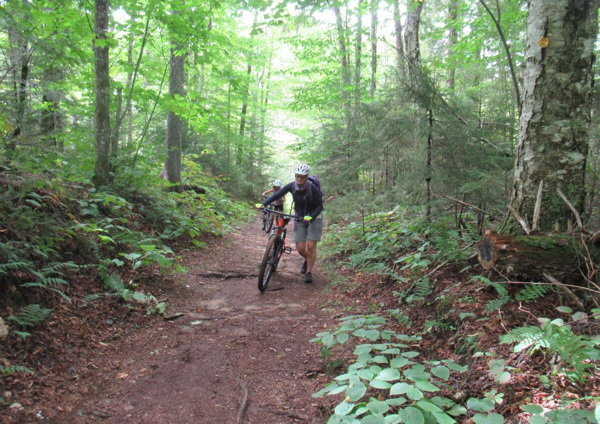 Outdoors writer Gillian Scott pushes her bike during a recent mountain bike outing near Inlet. (Herb Terns / Times Union)