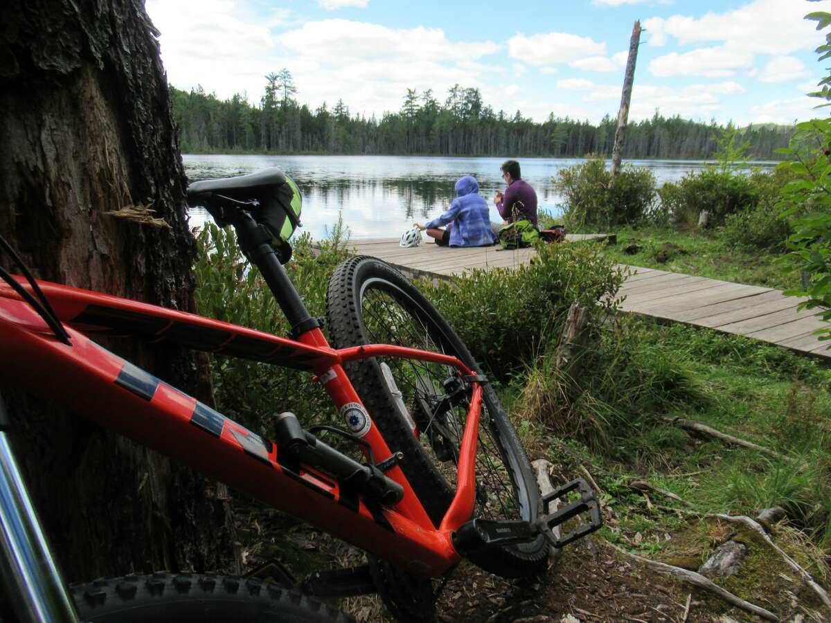 Outdoors writer Gillian Scott and her daughter relax lakeside after a mountain bike ride in the Moose River Plains area. (Herb Terns / Times Union)