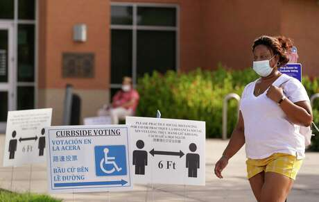 A woman leaves a polling location at Hiram Clarke Multi-Service Center during runoff voting amid the COVID-19 pandemic July 14 in Houston.
