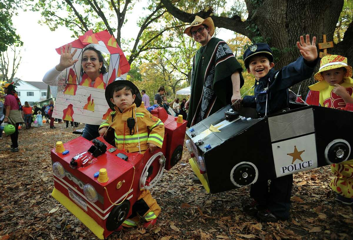Diane and Juan Prieto, of Bridgeport, and sons Martin, 4, left, and Matias, 5, wave to friends as the march in the costume parade at the Halloween on the Green event on the Fairfield Museum Commons in Fairfield, Conn. on Sunday, October 30, 2016.