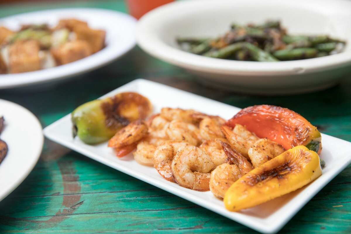 Kingston 11 Cuisine dishes include Wild Gulf Shrimp (foreground), Black Pepper Tofu, Sauteed string beans, and Plantains with vegan black bean sauce and sour cream. The restaurant, which features Jamaican food, is one of several participating in Oakland Restaurant (and More) Week in 2021.