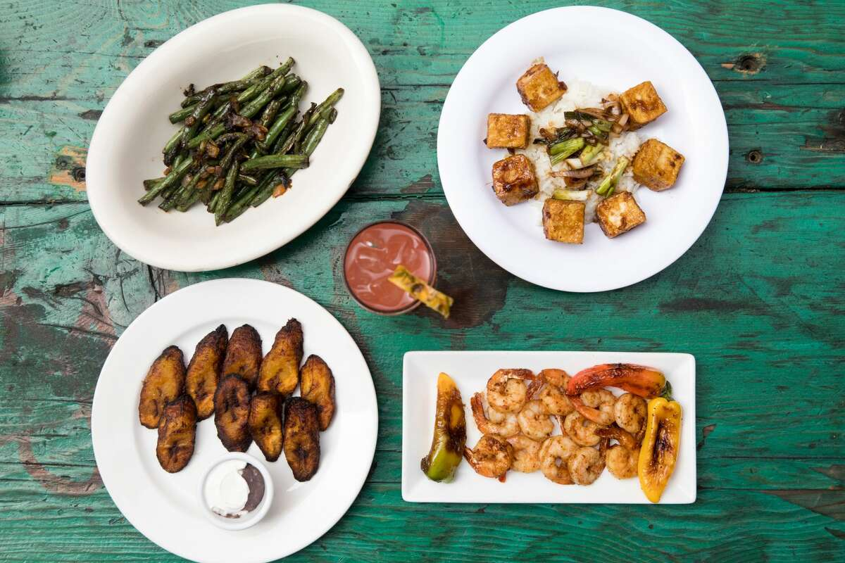 Kingston 11 Cuisine dishes include (clockwise from top left) sauteed string beans, black pepper tofu, wild gulf shrimp and plantains with vegan black bean sauce and sour cream. The restaurant, which features Jamaican food, is opening an outdoor patio space behind its restaurant in Oakland's Uptown neighborhood.