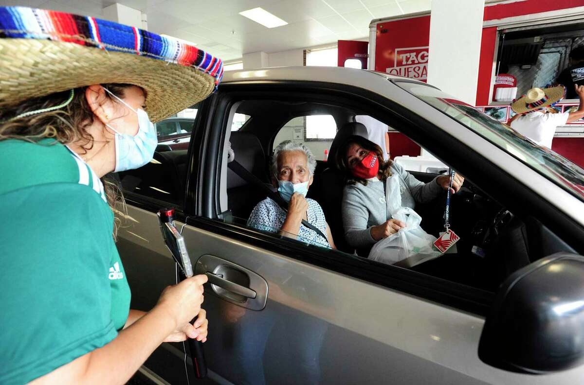 A volunteer greets Lilian Padilla, 88 and her daughter Patty Morales, 56, as they pick up free lunches during the Stamford Senior Center's monthly drive thru lunch program on Sept. 15, 2020 in Stamford, Connecticut. Over 150 lunches were prepared and handed out to Stamford Seniors. Taco Tuesday, the theme of the event, guests enjoyed two tacos (beef or chicken), rice, beans, salad and a drink. The meals were prepared by the crew from Tacos and Quesadillas food truck which serve up the Mexican delight to the sounds of cheers from the volunteers and staff of the Stamford Senior Center and the Staff of the Residence at Summer Street, who co-sponsored the event. The playing of Mariachi music filled the air with smiles from the many seniors and their caregivers who passed through.