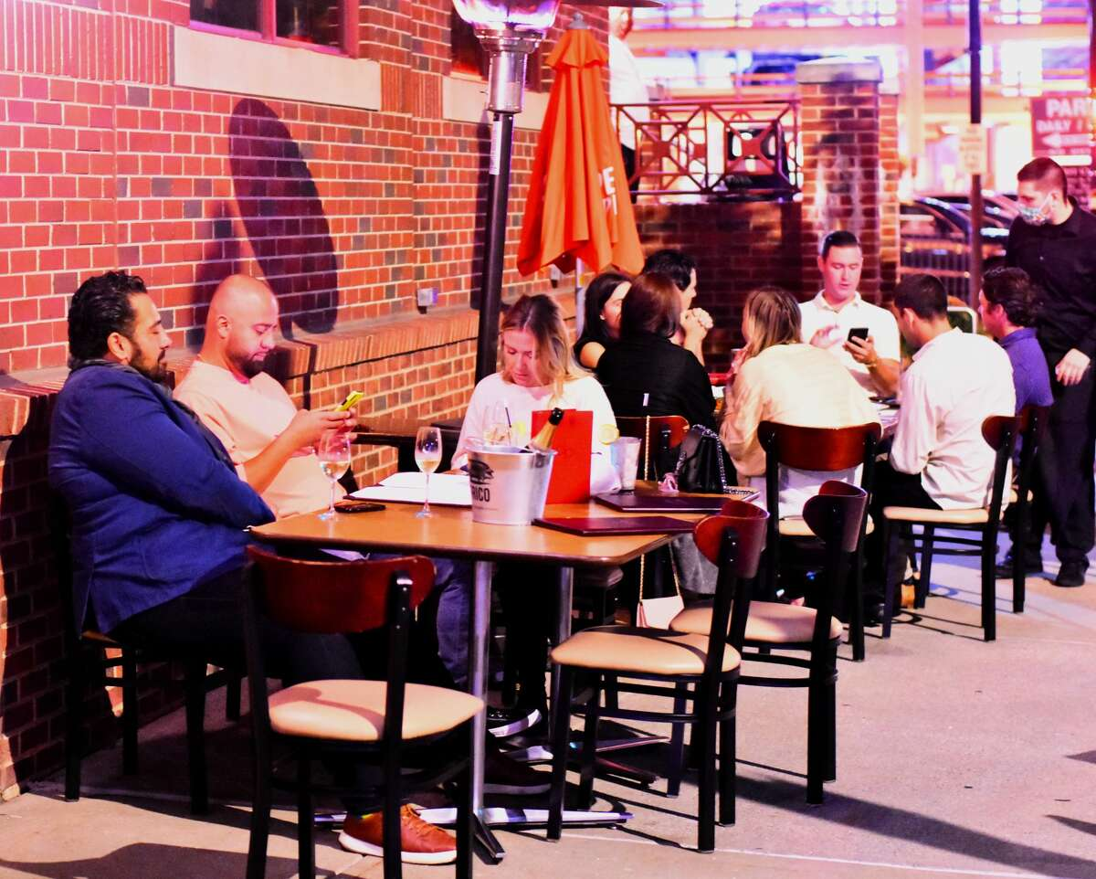 Patrons sit at sidewalk tables on Sheridan Avenue in downtown Albany alongside dp: An American Brasserie on Thursday, Sept. 17, 2020. Co-owner Dominick Purnomo is at far left. (Steve Barnes/Times Union)