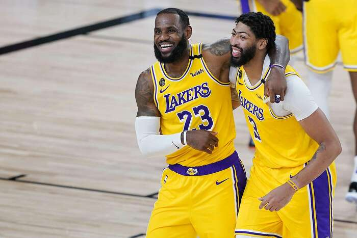 The Los Angeles Lakers' LeBron James (23) and Anthony Davis (3) celebrate after a win against the Denver Nuggets at The Arena at ESPN Wide World Of Sports Complex on August 10, 2020, in Lake Buena Vista, Florida. (Ashley Landis/Pool/Getty Images/TNS)