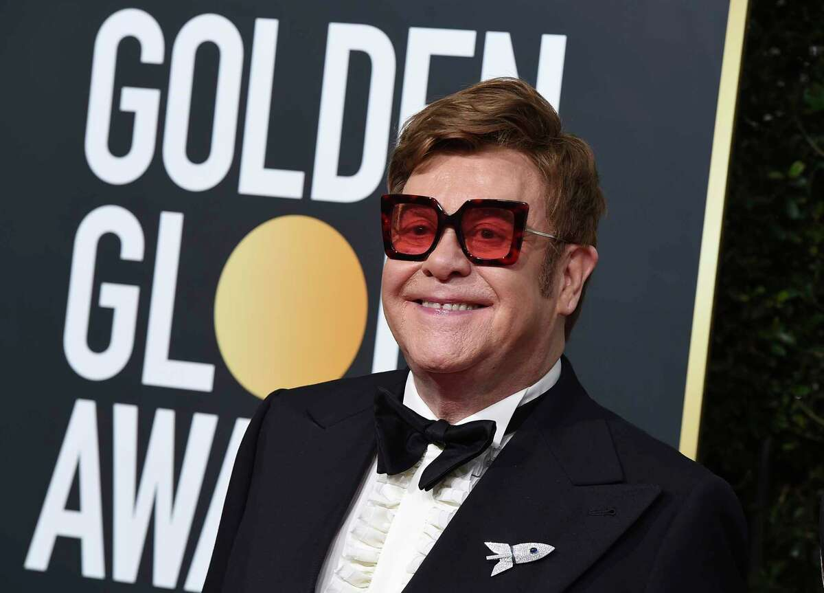 FILE - In this Jan. 5, 2020 file photo, Elton John arrives at the 77th annual Golden Globe Awards at the Beverly Hilton Hotel, in Beverly Hills, Calif. An emotional John had to cut short a performance in New Zealand on Sunday, Feb. 16 after he lost his voice due to walking pneumonia and had to be assisted off stage. John reached out to his fans on Instagram on Sunday, apologizing for ending his show at Auckland's Mt Smart Stadium early. (Photo by Jordan Strauss/Invision/AP, File)