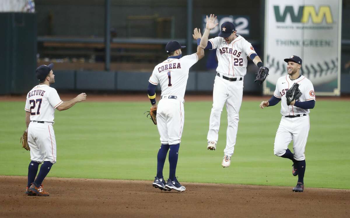 Houston Astros Jose Altuve, Carlos Correa, Josh Reddick and George Springer celebrate the Astros 2-1 win over the Texas Rangers after an MLB baseball game at Minute Maid Park, Thursday, September 17, 2020, in Houston.