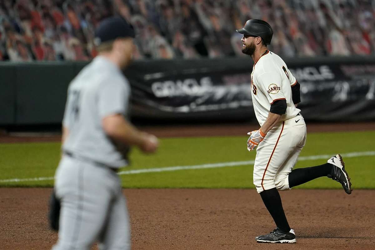 San Francisco Giants' Brandon Belt, right, rounds the bases after hitting a two-run home run off of Seattle Mariners pitcher Ljay Newsome, left, during the third inning of a baseball game in San Francisco, Wednesday, Sept. 16, 2020. This is a makeup of a postponed game from Tuesday in Seattle. (AP Photo/Jeff Chiu)
