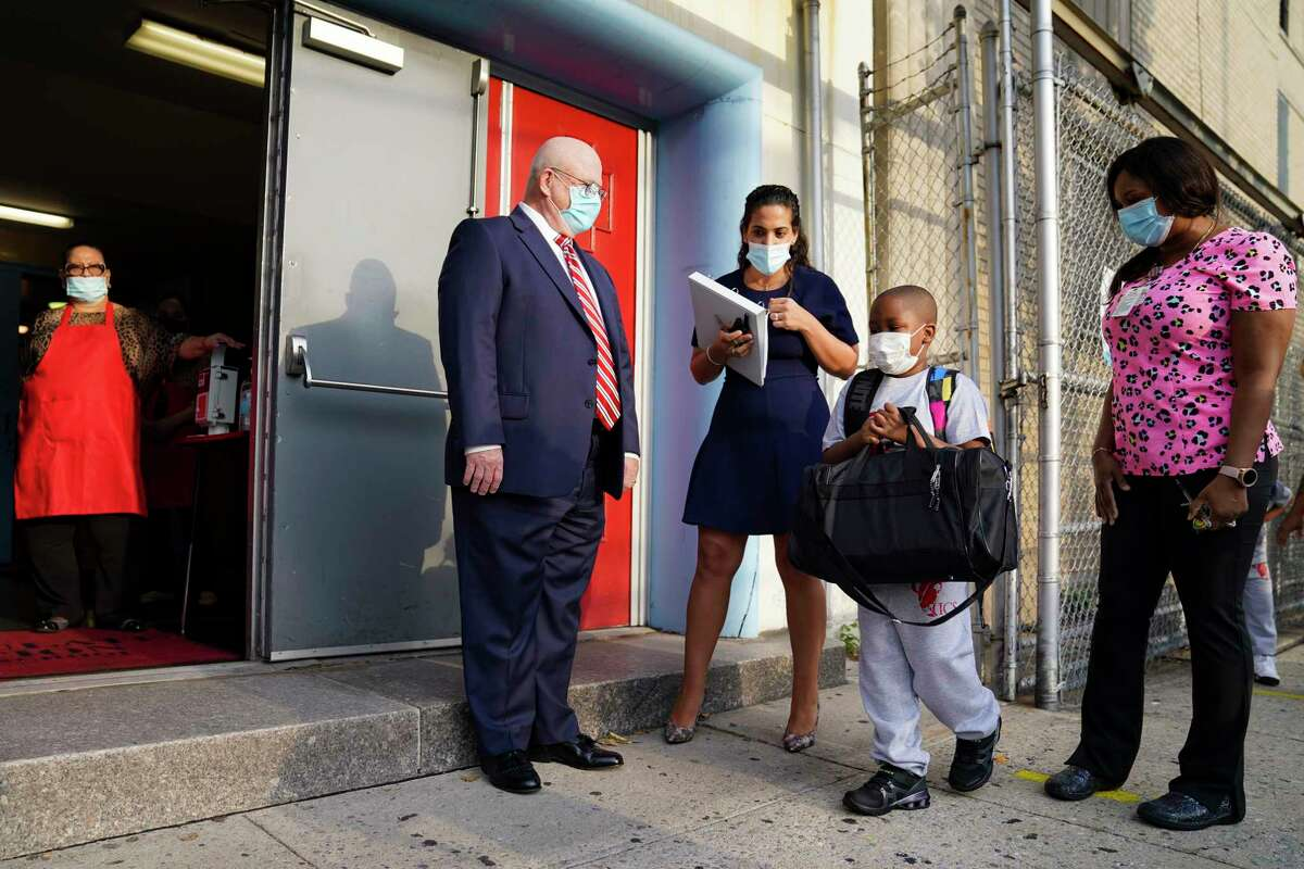 FILE - In this Sept. 9, 2020, file photo, Michael J. Deegan, Superintendent of Schools for the Archdiocese of New York, center left, greets students as they wear protective masks while arriving for classes at the Immaculate Conception School in The Bronx borough of New York. New York City has again delayed the planned start of in-person learning for most of the more than 1 million students in its public school system. Mayor Bill de Blasio announced Thursday, Sept. 17, that most elementary school students would do remote-only learning until Sept. 29. Middle and high schools would stay remote through Oct. 1.(AP Photo/John Minchillo)