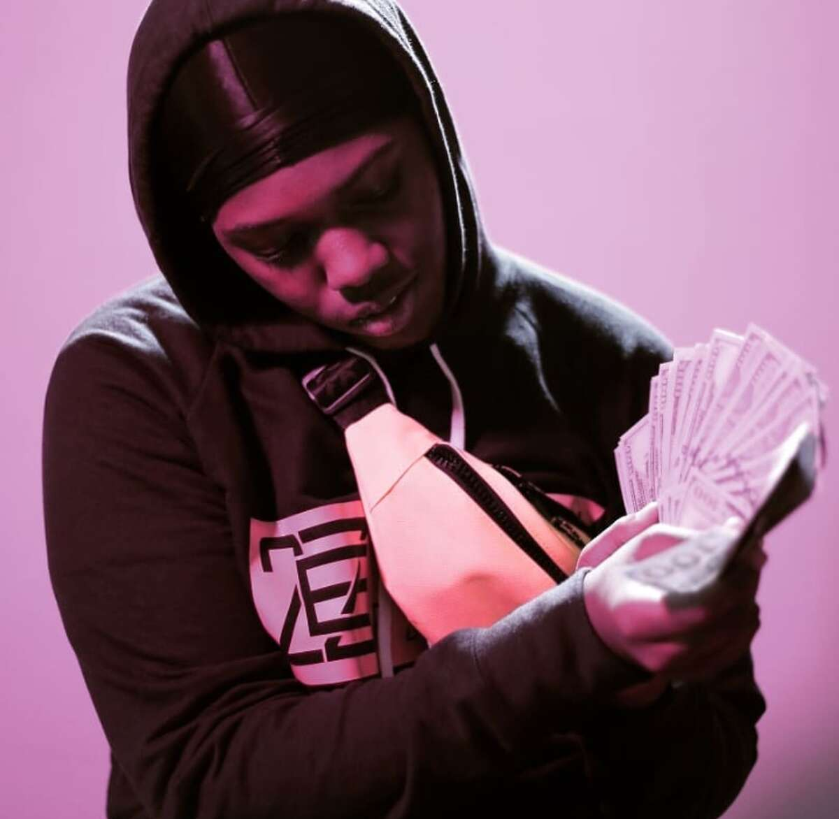 ZaniefWashington holds fake money at a photo shoot at Youth FX, an organization that empowers young people in the Capitol Region through media arts and digital film.