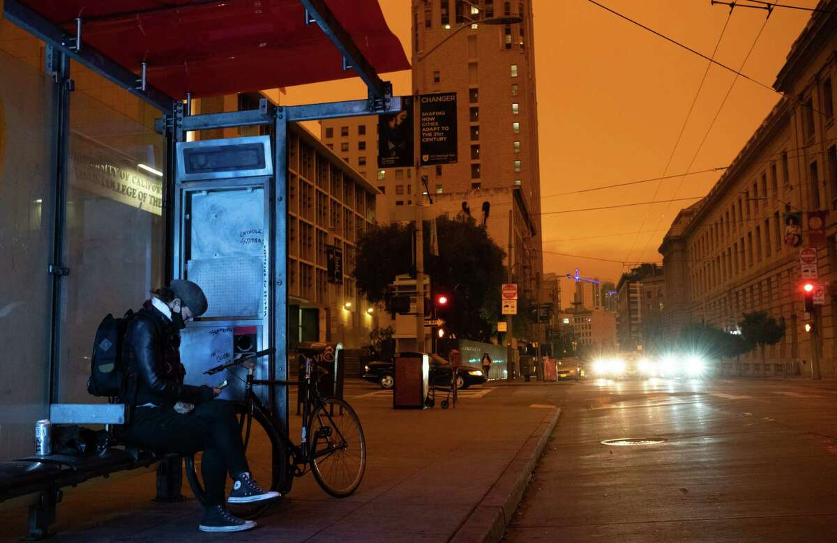A person waits at a bus stop around noon Sept. 9 in San Francisco.