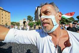 "A man wearing a cut out face mask takes part in a protest of ""No Mask"" movements, Covid deniers movements, anti-5G movements and anti-vaccination movements against the government's health policy on Sept. 5, 2020 in Rome during the COVID-19 infection, caused by the novel coronavirus."
