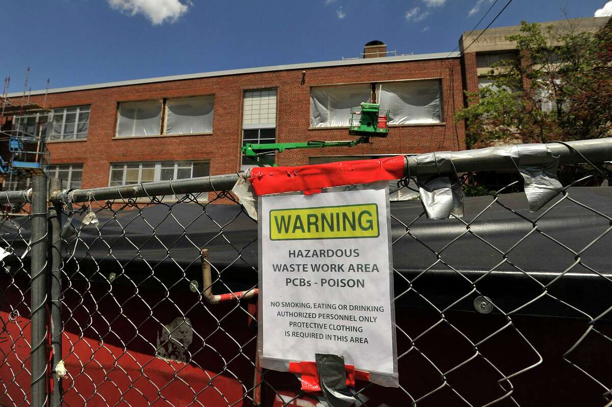 A dumpster of hazardous waste sits in front of a middle school as construction work continues on the facade of the school in 2015.