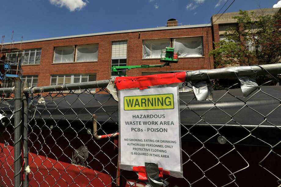 A dumpster of hazardous waste sits in front of a middle school as construction work continues on the facade of the school in 2015. Photo: File Photo / Stamford Advocate