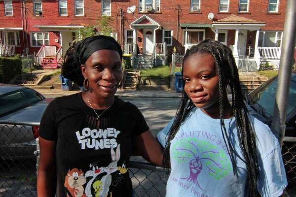 Sha'Nia Cooper, 15, right, poses with her mom Erika Cooper at their home in Waterbury, Conn., on Tuesday Sept. 1, 2020. Sha'Nia was arrested at school after getting into a fight in 2019. Waterbury consistently has the highest school based arrest rate, at three times the state average.