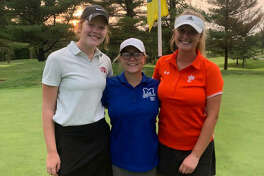 Triad's Emma Hill, left, Marquette's Audrey Cain, center, and Edwardsville's Riley Burns first played golf together nine years ago. On Wednesday, they played their first high school match together.